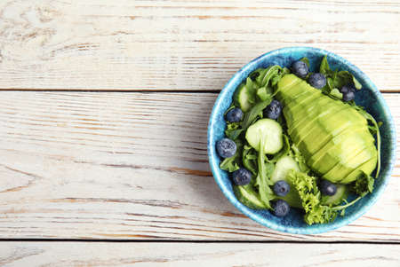 Delicious avocado salad with blueberries in bowl on white wooden table, top view. Space for text