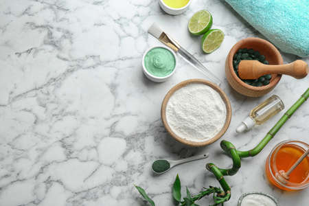 Flat lay composition with spirulina facial mask and ingredients on marble table, space for text