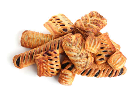 Heap of fresh tasty puff pastries on white background, top view