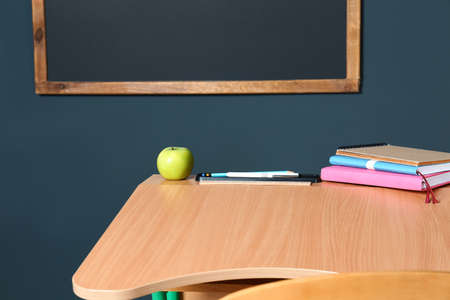 Wooden school desk with stationery and apple near blackboard on grey wall