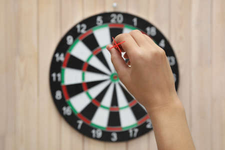 Woman throwing red arrow at dart board on wooden background, closeup Фото со стока