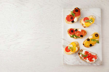 Marble board with delicious tomato bruschettas on white wooden background, top view. Space for text Stockfoto