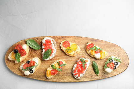 Wooden board with delicious tomato bruschettas on light grey background, top view