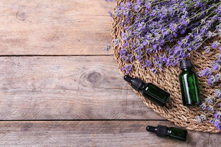 Bottles of essential oil and lavender flowers on wooden background, flat lay. Space for text 写真素材