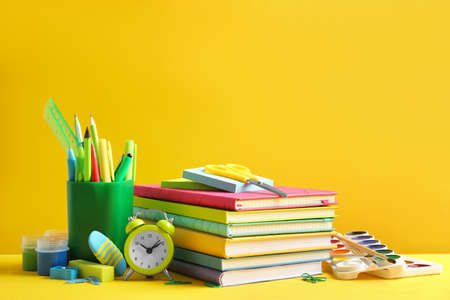 Different school stationery on yellow background