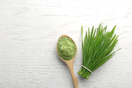 Spoon of wheat grass powder and green sprouts on white wooden table, flat lay. Space for text Stockfoto