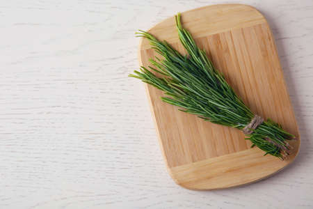 Board with bundle of fresh rosemary twigs on white wooden background, top view. Space for text Stockfoto