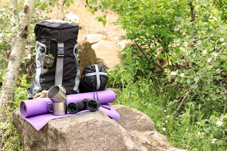 Backpack and camping equipment on stone in forest. Space for text Zdjęcie Seryjne
