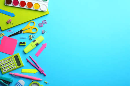 Colorful school stationery on light blue background, flat lay. Space for text Фото со стока