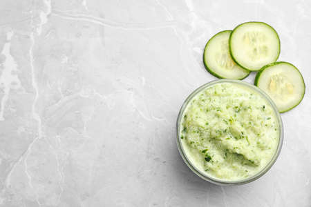 Handmade face mask and cucumber slices on light marble table, flat lay. Space for text Stockfoto