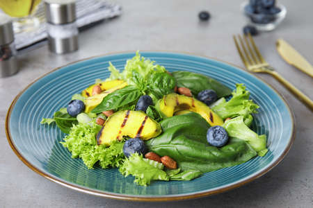 Delicious avocado salad with blueberries on grey table