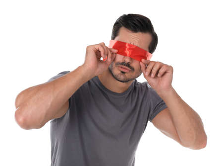 Young man wearing red blindfold on white background