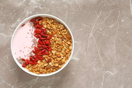 Smoothie bowl with goji berries on beige marble table, top view Stockfoto