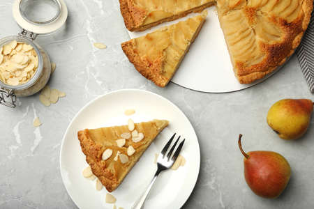 Cut delicious sweet pear tart and almond flakes on grey marble table, flat lay Stockfoto