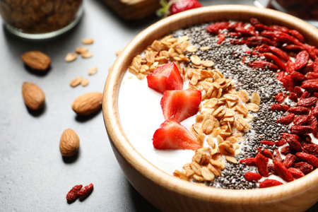 Smoothie bowl with goji berries on grey table, closeup