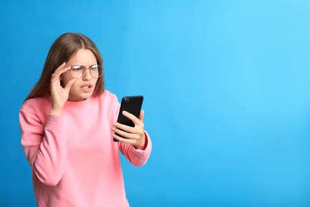 Jeune femme ayant des problèmes de vision utilisant un smartphone sur fond bleu, espace pour le texte Banque d'images