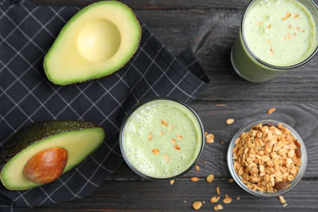 Glasses of tasty smoothie with avocado and oatmeal on black wooden table, flat lay
