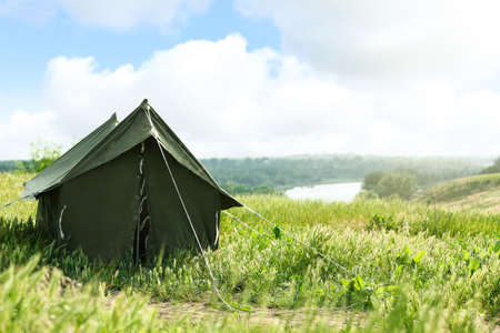 Camping tent in green field on sunny day. Space for text Zdjęcie Seryjne