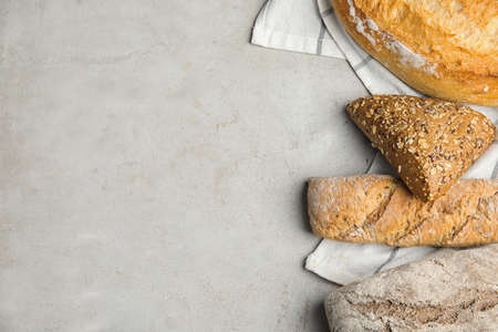 Loaves of different breads on light background, flat lay. Space for text