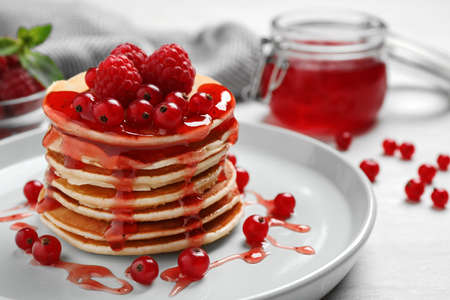 Delicious pancakes with fresh berries and syrup on white table