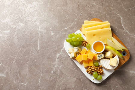 Board with different kinds of delicious cheese and snacks on marble background, top view. Space for text