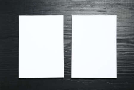 Blank paper sheets for brochure on black wooden background, flat lay. Mock up