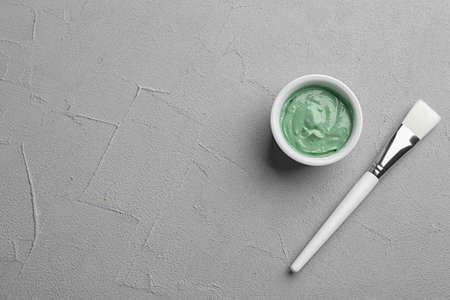 Spirulina facial mask and brush on light grey table, flat lay. Space for text