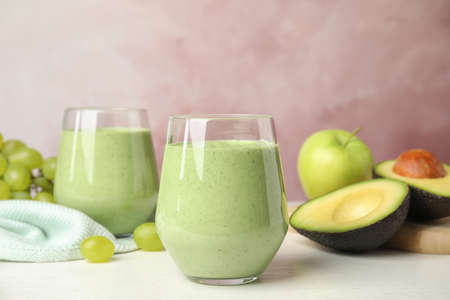 Glasses of tasty avocado smoothie and ingredients on white wooden table against pink background