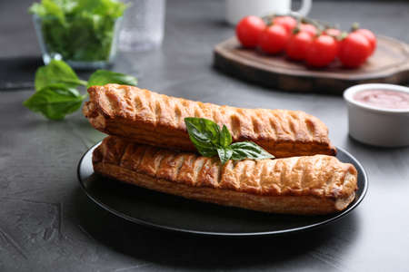 Fresh delicious puff pastry served on grey table