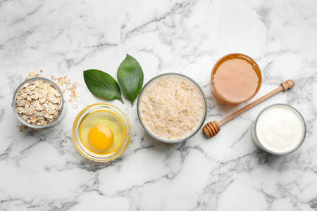 Handmade face mask and different ingredients on white marble table, flat lay