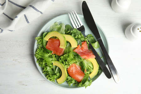 Delicious avocado salad with salmon on white wooden table, flat lay