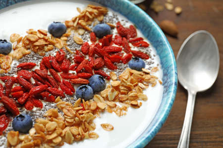 Smoothie bowl with goji berries and spoon on wooden table, closeup