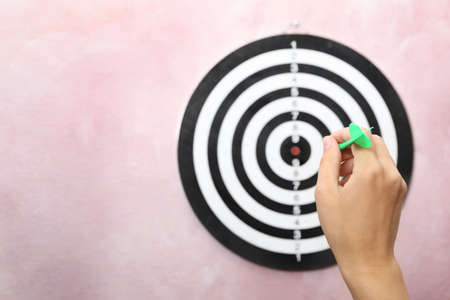 Woman throwing green arrow at dart board on pink background, closeup. Space for text