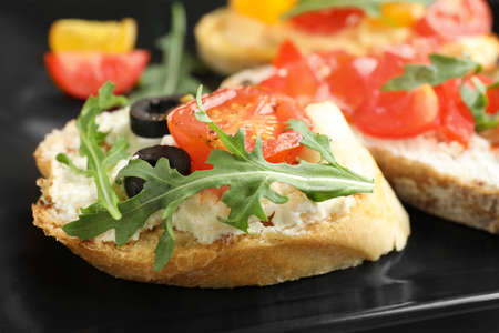 Delicious tomato bruschetta on black plate, closeup
