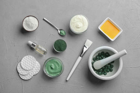Flat lay composition with spirulina facial mask and ingredients on light grey table