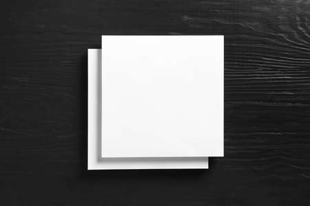 Stack of blank paper sheets for brochure on black wooden background, top view. Mock up Stockfoto - 129232326