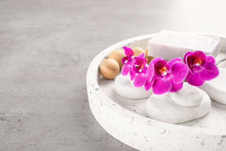 Tray with spa stones, orchid flowers and soap on grey table