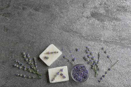 Flat lay composition with hand made soap bars and lavender flowers on grey stone table. Space for text