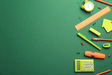 Bright school stationery on green background, flat lay. Space for text Фото со стока