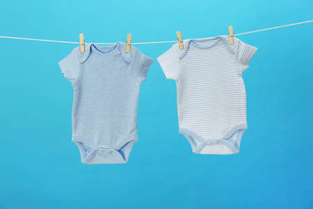 Baby clothes hanging on clothes line against blue background. Laundry day