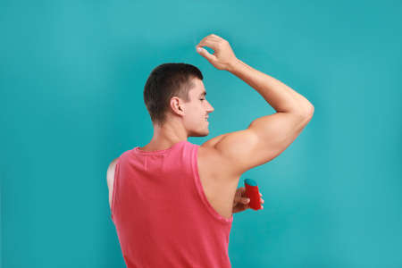 Young man applying deodorant to armpit on light blue background 写真素材