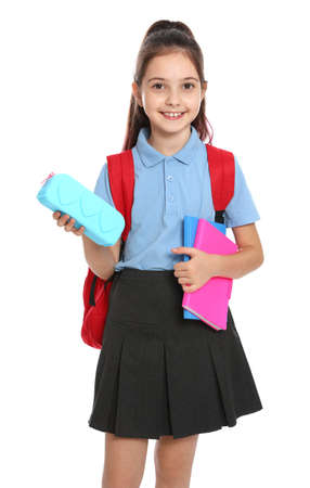 Cute little girl in school uniform with backpack and stationery on white background