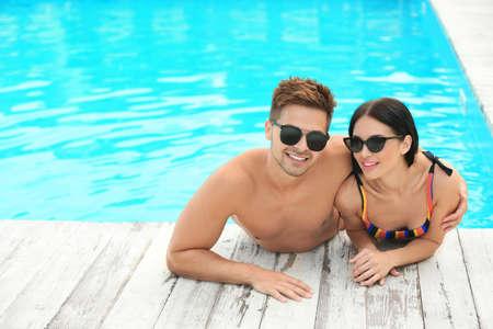 Mujer en bikini con su novio en el resort. Feliz, pareja joven