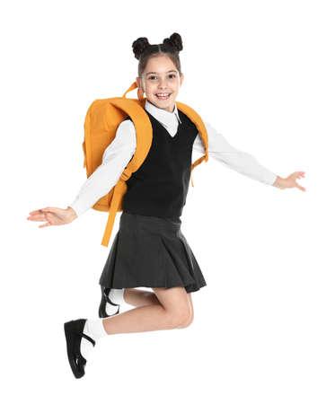 Fille heureuse en uniforme scolaire sautant sur fond blanc