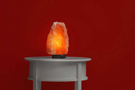 Himalayan salt lamp on table against dark red background