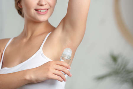 Young woman applying roll-on deodorant indoors, closeup