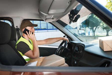 Jeune coursier parlant au téléphone dans la voiture de livraison