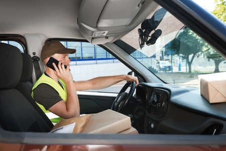 Young courier talking on phone in delivery car