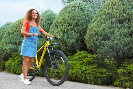 Beautiful young African-American woman with bicycle on city street Archivio Fotografico