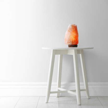 Himalayan salt lamp on table against  white wall. Space for text